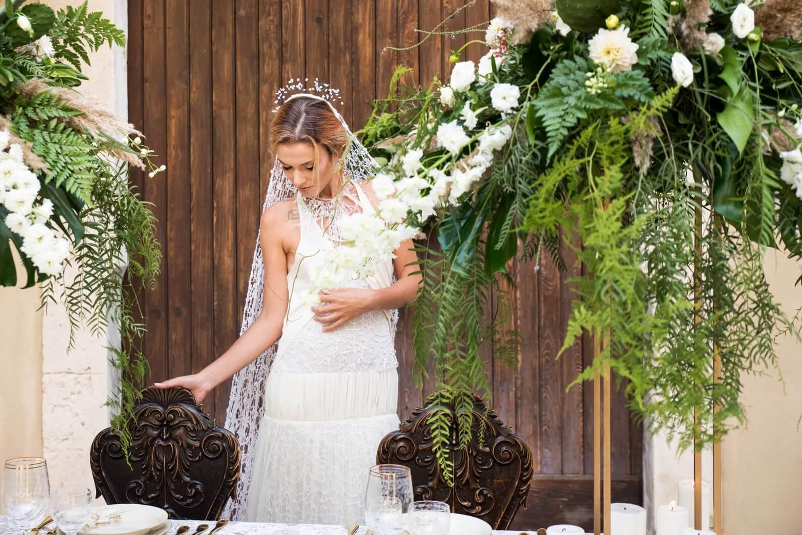 Sposa con abito bianco in pizzo e velo lungo
