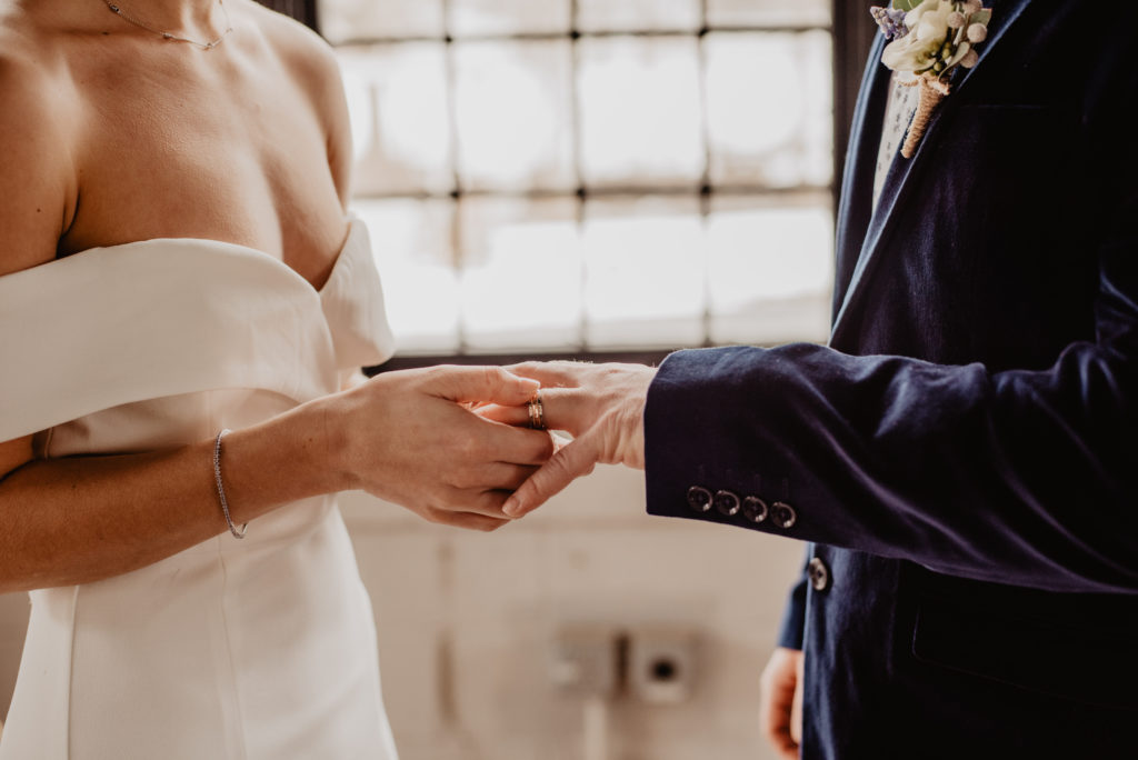 Woman Putting Wedding Ring on Groom's Finger