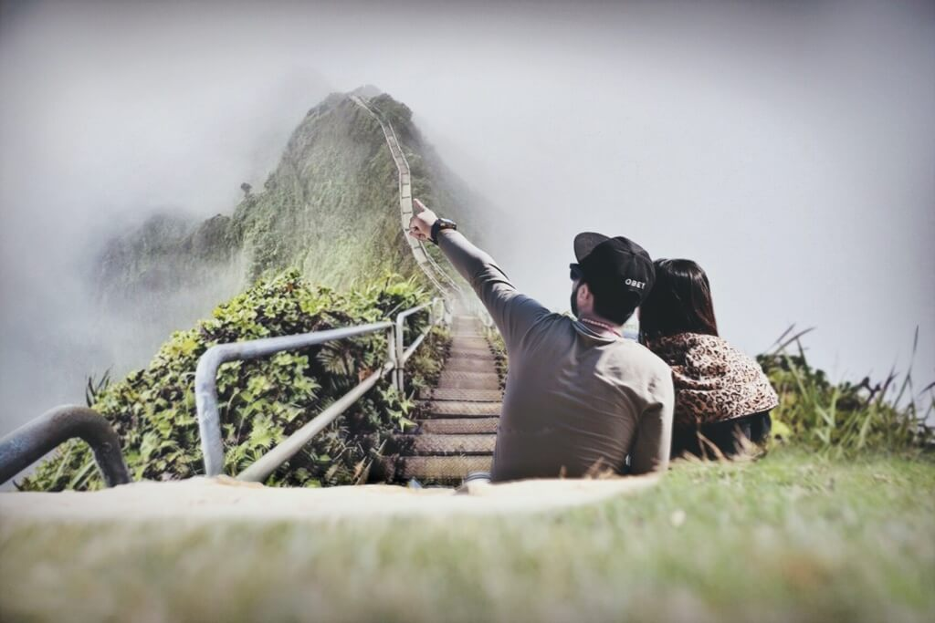 fotografia di una coppia seduta su l'erba verde vicino ad un ponte