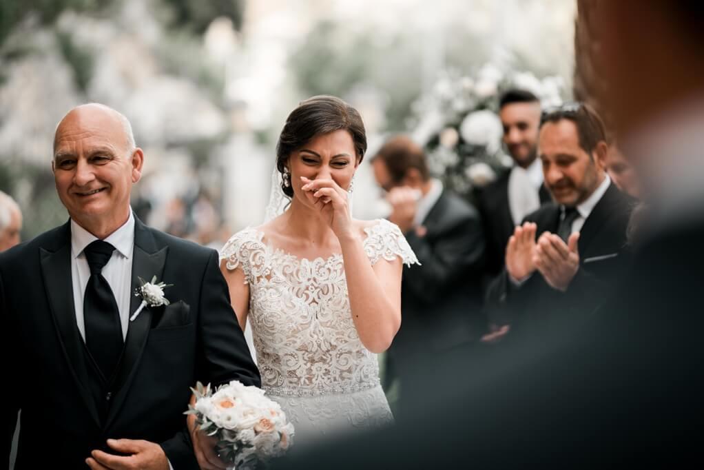 la sposa si emoziona e piange mentre il padre l'accompagna all'altare