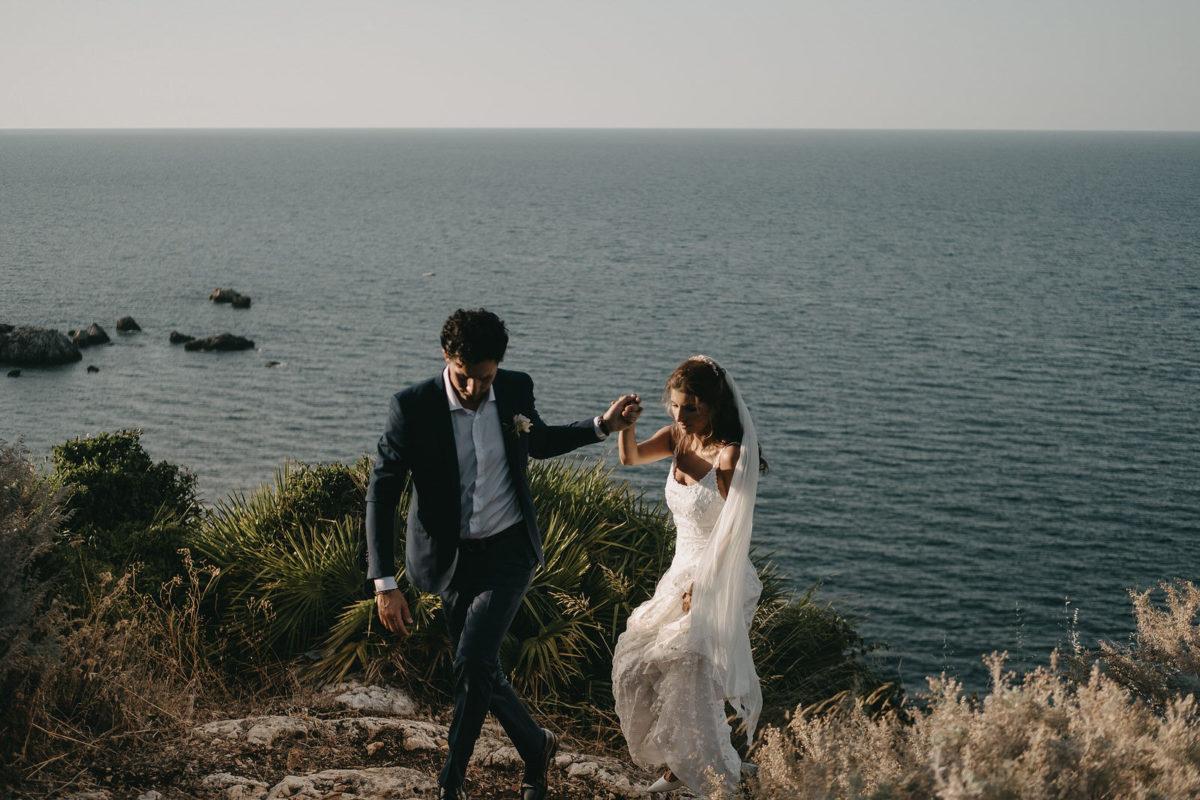 Coppia di sposi mano nella mano sul mare di Sicilia